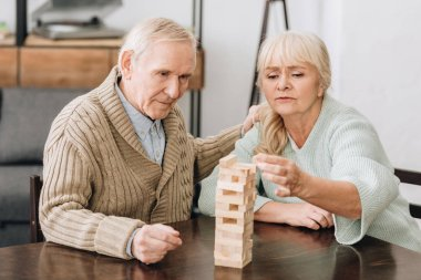retired couple playing jenga game on table at home