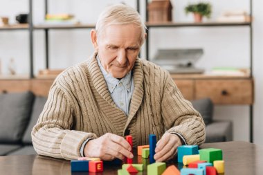 senior man playing with wooden toys at home