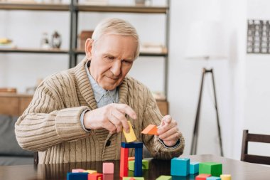 retired man playing with wooden toys at home