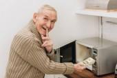 Veselý senior muž uvedení prst na rty říct ticho při ukládání peněz v mikrovlnné troubě