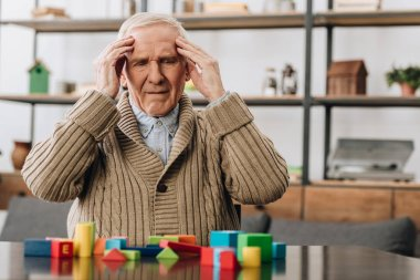 pensioner having headache while sitting near wooden toys