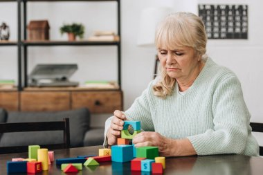senior woman playing with wooden toys at home