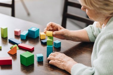 senior woman playing with wooden cubes on table