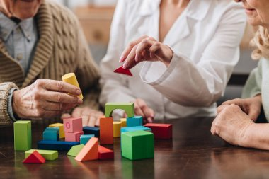cropped view of retired couple and caregiver playing with wooden toys