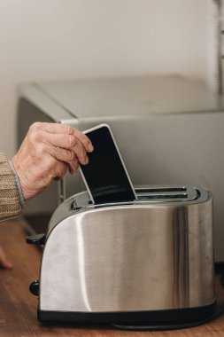 cropped view of senior man putting smartphone in toaster