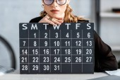 businesswoman in black clothes and glasses holding calendar