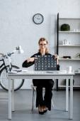Fotografie atraktivní podnikatelka v černém oblečení a brýle zobrazující kalendáře