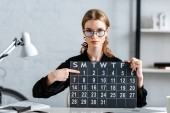 atraktivní podnikatelka v černém oblečení a brýle drží kalendáře a zobrazení data