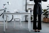 Fényképek Üzletasszony fekete ruhában, asztal és szék közelében levágott látképe