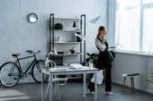 Geschäftsfrau in offizieller Kleidung wirft am Arbeitsplatz Dokumente in die Luft
