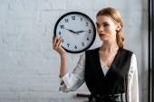 Fotografie Selektivní fokus krásné vážné ženy ve formální oblečení drží hodiny