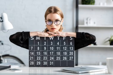 beautiful businesswoman in black clothes and glasses sitting on chair and holding a calendar