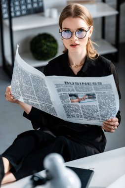Beautiful businesswoman in black clothes and glasses sitting at table and holding newspaper while looking at camera stock vector