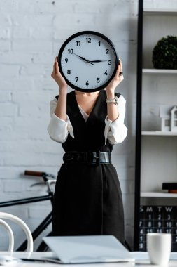 selective focus of businesswoman in formal wear holding clock in front of face at workplace