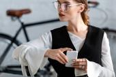 krásná obchodnice v formální oblečení a brýlí pomocí smartphone na pracovišti