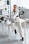 Photo businesswoman in white formal wear sitting on desk with laptop at workplace while looking at camera