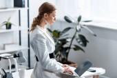 Koncentrovaná podnikatelka v bílém formální oblečení sedí na stole a pomocí přenosného počítače na pracovišti