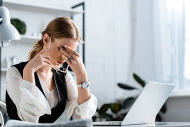 businesswoman in formal wear sitting at computer desk, touching forehead and suffering from headache at workplace