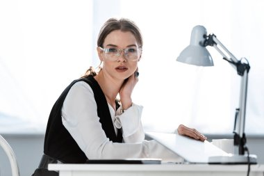 Beautiful businesswoman in formal wear sitting at computer desk at workplace stock vector