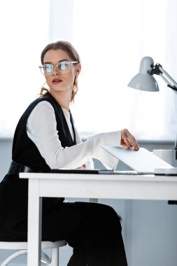 Businesswoman in formal wear sitting at computer desk and looking away at workplace stock vector