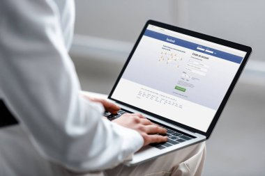 cropped view of woman using laptop with facebook website on screen