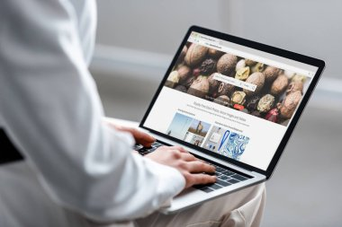cropped view of woman using laptop with depositphotos website on screen