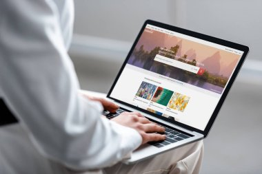 cropped view of woman using laptop with shutterstock website on screen