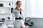 usměvavá podnikatelka v bílém formální oblečení na smartphone na pracovišti