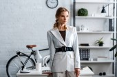koncentrované podnikatelka v bílém formální oblečení v moderních kancelářských interiérů
