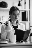 black and white photo of businesswoman in formal wear sitting at desk and reading notebook at workplace