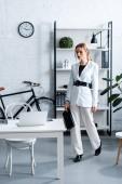 vážnou podnikatelka v bílém formální oblečení drží notebook v moderních kancelářských interiérů
