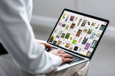 cropped view of woman using laptop with pinterest website on screen