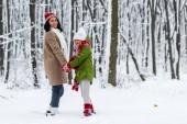 afro-amerikai anya és lánya, mosolyogva, a kézen és a látszó-on fényképezőgép, winter Park