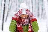 Fotografie Lächelndes afrikanisch-amerikanisches Kind mit Strickmütze bei Schneefall im Winterpark über die Augen gezogen