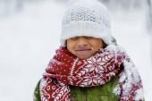 Fotografie lächelndes afrikanisch-amerikanisches Kind in warmer Kleidung mit Strickmütze, die im Winter über die Augen gezogen wird