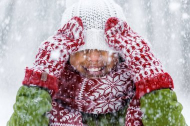 Close up view of smiling african american child with knitted hat pulled over eyes during snowfall stock vector