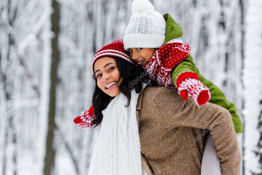 attractive african american mother giving piggyback ride to cute daughter  in winter park