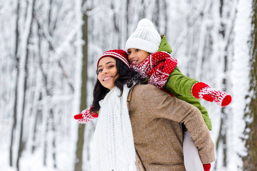 attractive african american woman giving piggyback ride to smiling daughter in winter park