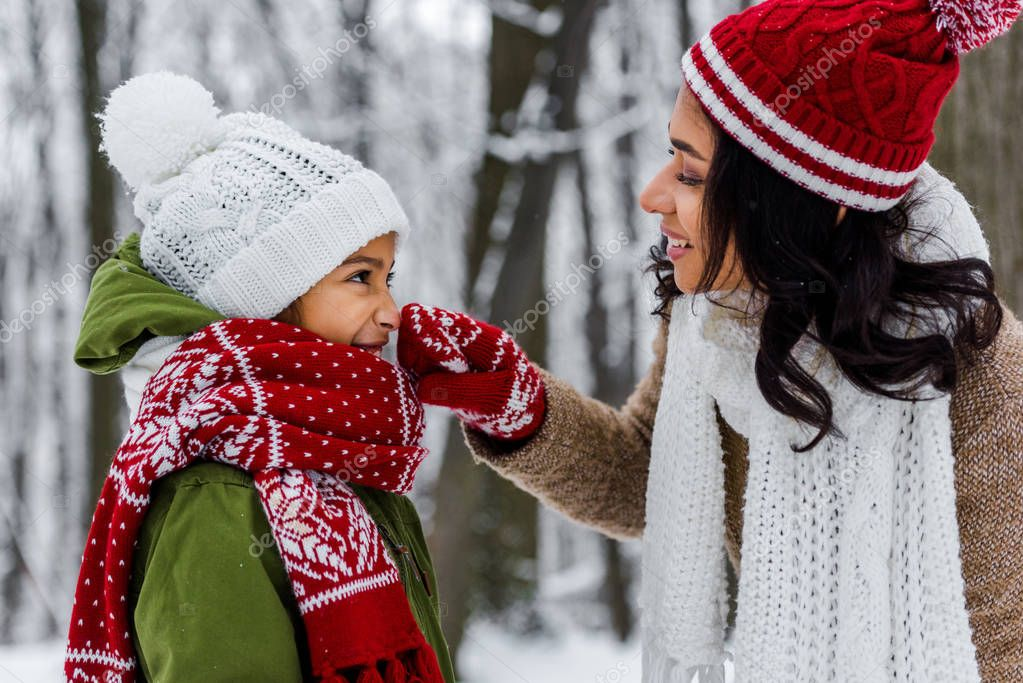 attractive african american woman touching nose of cute preteen daughter in winter park