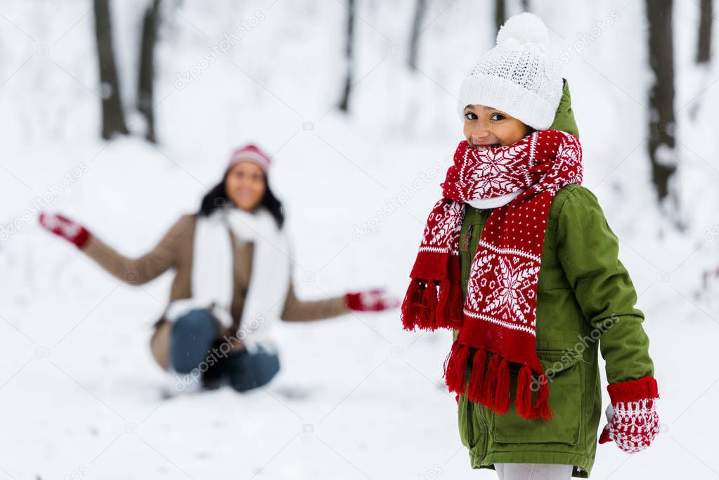 cute child looking at camera and african american mother at background in winter park