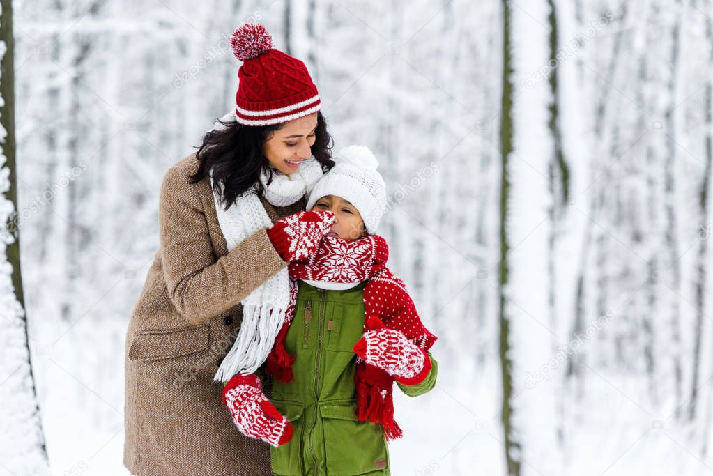 cheerful african american mom touching nose of cute daughter in winter park