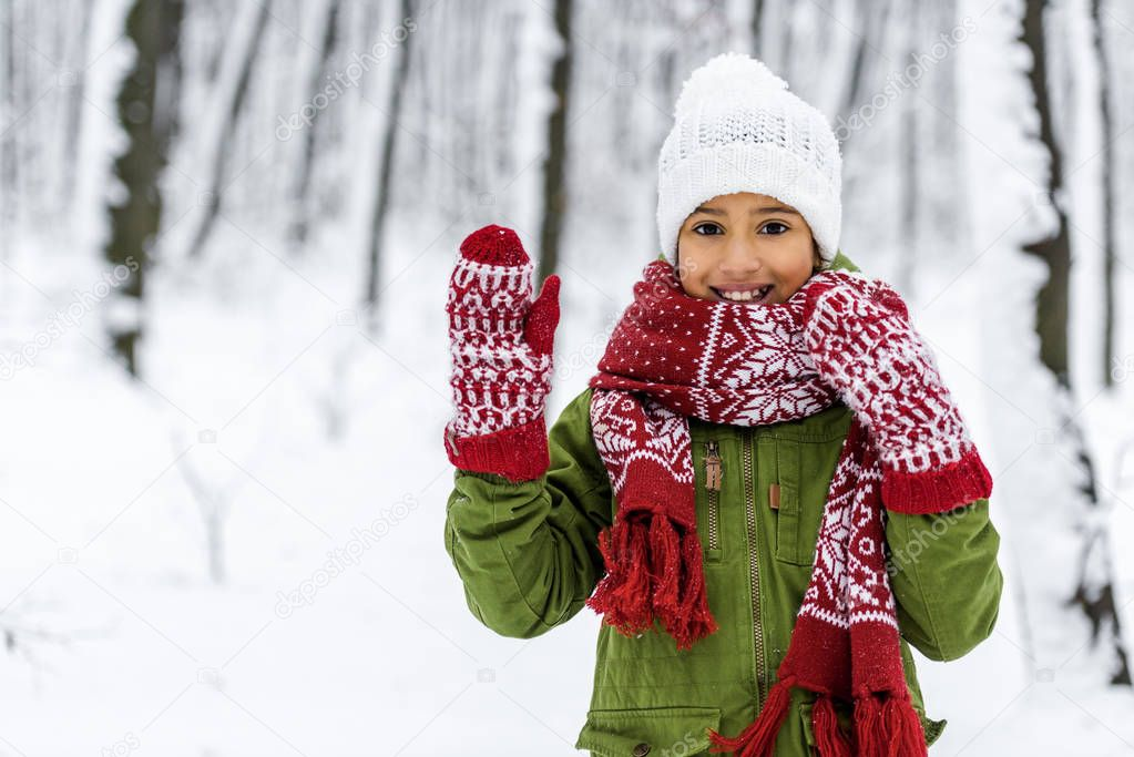 african american child in warm clothing smiling, waving with hand and looking at camera in winter park