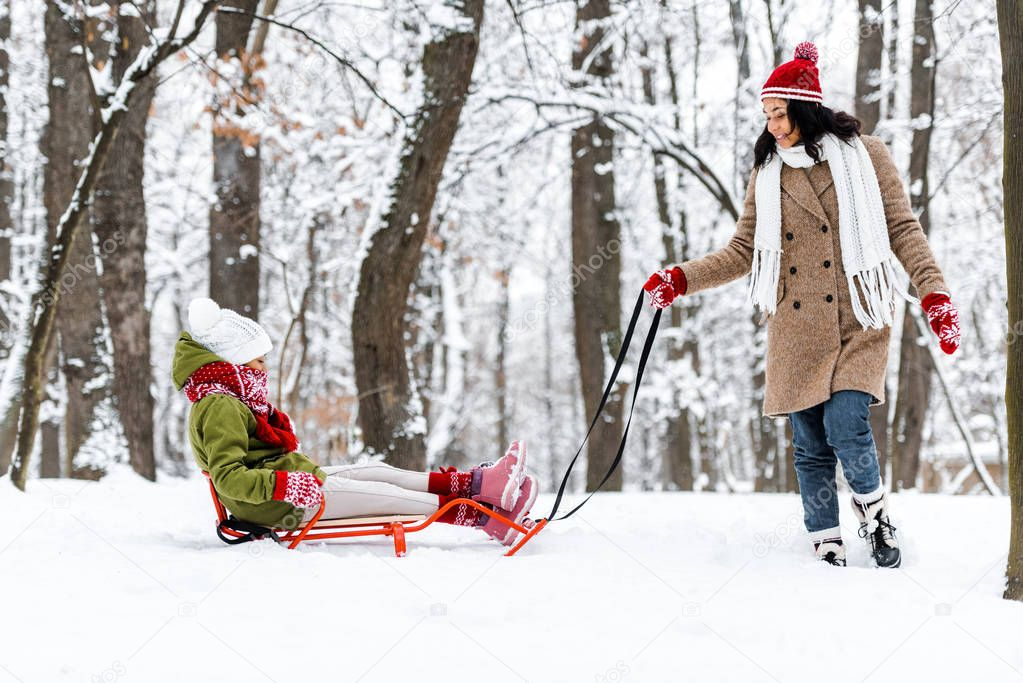 attractive african american woman pulling daughter on sledge in winter park