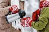 Fotografia ritagliate la vista di donna versando tè dal thermos in tazza rossa che tiene da bambino in inverno