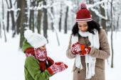 Photo attractive african american mother and cute daughter holding cups of tea in snowy forest