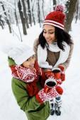 vonzó afro-amerikai anya és aranyos lánya gazdaság piros csésze tea tartózkodásuk alatt havas erdei fák közelében
