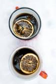 Fotografie červené šálky čaje s citronem, který pobývá na bílém sněhu