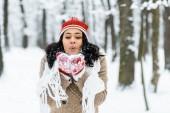 attraktive Afroamerikanerin bläst Schnee in der Nähe von Bäumen im Winterwald