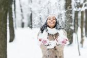 attraktive Afroamerikanerin wirft Schnee in Park und lächelt im Winterwald