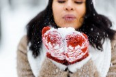 cropped view of beautiful african american woman blowing snow in winter forest and looking at snow